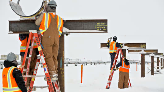 Workers position a mounting shoe for a pipeline under construction outside a BP Plc production facility in Prudhoe Bay, Alaska, U.S., on Thursday, Feb. 16, 2017.