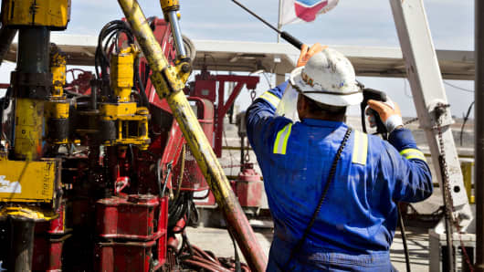 A Nabors Industries worker uses a power washer to clean the floor of a rig drilling for Chevron in the Permian Basin near Midland, Texas, March 1, 2018.