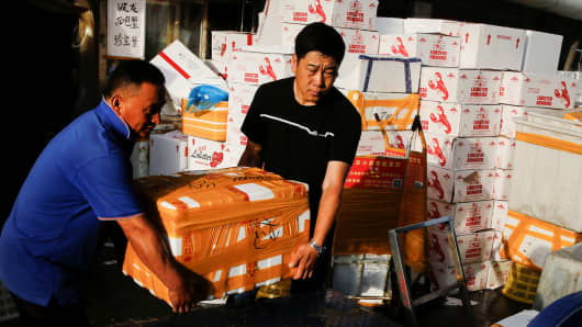 Men put a box containing lobsters imported from the U.S. onto the back of a vehicle at a fish market in Beijing, China.