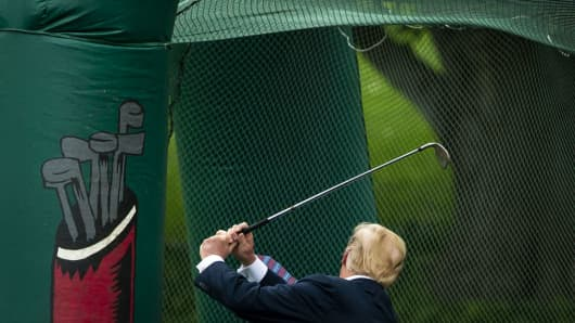 U.S. President Donald Trump swings a golf club during the White House Sports and Fitness Day event in Washington, D.C., U.S., on May 30, 2018.