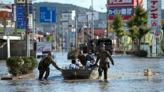 Soldiers ferry people to safety following heavy flooding, on July 8, 2018 in Kurashiki near Okayama, Japan.