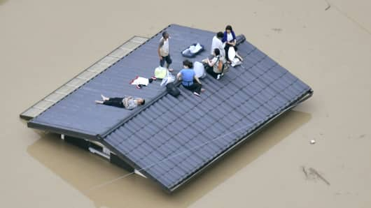 An aerial view shows local residents seen on the roof of submerged house at a flooded area as they wait for a rescue in Kurashiki, southern Japan on July 7th, 2018.
