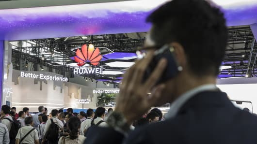 An attendee uses a mobile phone while standing in front of the Huawei Technologies Co. booth at the Mobile World Congress Shanghai in Shanghai, China, on Thursday, June 28, 2018. The exhibition runs through June 29.