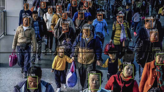 Monitors display a video showing facial recognition software in use at the headquarters of the artificial intelligence company Megvii, in Beijing, May 10, 2018. Beijing is putting billions of dollars behind facial recognition and other technologies to track and control its citizens.