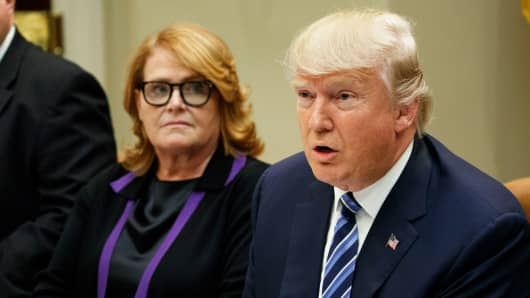 Sen. Heidi Heitkamp, D-N.D., left, listens as President Donald Trump speaks in the Roosevelt Room of the White House in Washington.