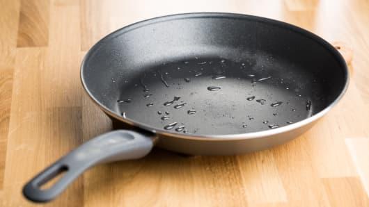 Teflon frying pan on wooden table