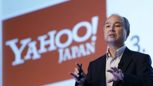 SoftBank CEO Masayoshi Son speaks in front of a screen displaying the Yahoo Japan logo.