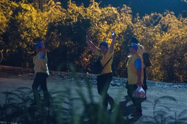Thai volunteers celebrate while leaving the Tham Luang cave area as all 12 boys and their coach who became trapped in a flooded Thai cave more than a fortnight ago have been rescued, the Navy SEALs announced on July 10, completing an astonishing against-the-odds rescue mission that has captivated the world.