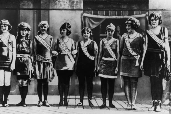 Full-length portrait of the first Miss America contestants, wearing their sashes over swimsuits, standing in a line on the boardwalk in Atlantic City, New Jersey.