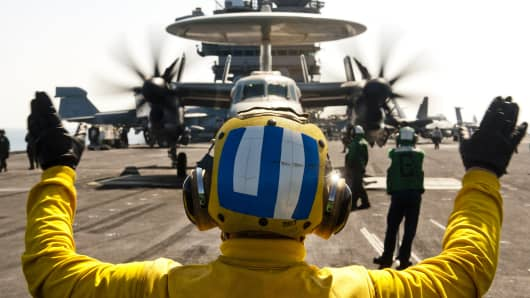 U.S. Navy Aviation Boatswain's Mate directs an E-2C Hawkeye aircraft on the flight deck of the aircraft carrier USS John C. Stennis.