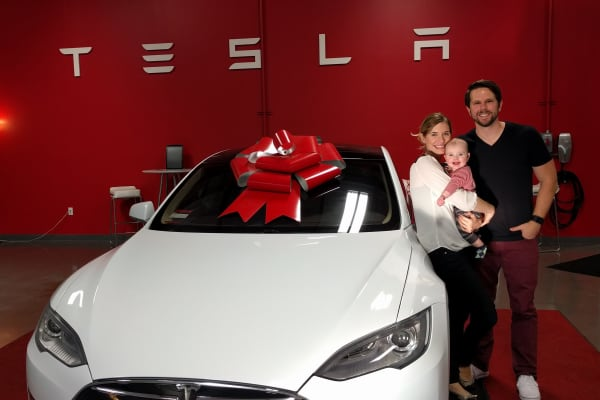 YouTuber Ben Sullins (R) stands with his wife (L) and their son during their Model S delivery on January 16, 2016.