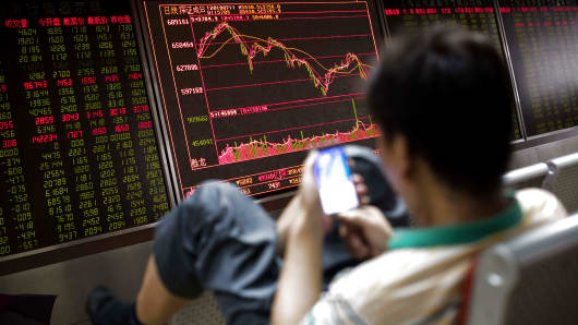 A man sits in front of a screen showing stock prices at a securities company in Beijing on July 11, 2018. (Photo by NICOLAS ASFOURI / AFP)        (Photo credit should read NICOLAS ASFOURI/AFP/Getty Images)