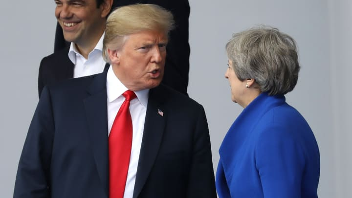 U.S. President Donald Trump, left, speaks with Theresa May, U.K. prime minister, as world leaders gather for a family photograph during the North Atlantic Treaty Organization (NATO) summit at the military and political alliance's headquarters in Brussels, Belgium, on Wednesday, July 11, 2018.
