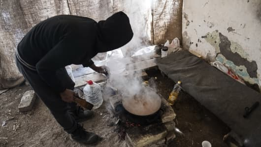 Preparing food on an open fire, a migrant from Pakistan cooks a meal for his friends in Serbia. (Photo by Edward Crawford/SOPA Images/LightRocket via Getty Images)