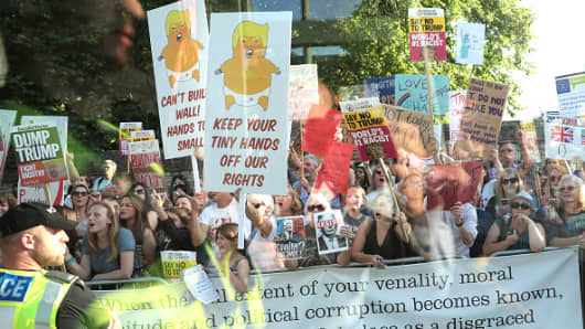 Protesters seen from a coach window hold up placards along the route at Blenheim Palace prior the arrival of U.S. President Donald Trump and First Lady Melania Trump on July 12, 2018 in Woodstock, England.