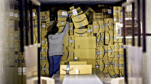 An employee unloads a truck load of Amazon.com packages at the United Parcel Service (UPS) Chicago Area Consolidation Hub in Hodgkins, Illinois.