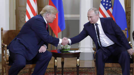 President Donald Trump (L) and Russia's President Vladimir Putin shake hands during a meeting at the Presidential Palace, Helsinki, July 16, 2018.