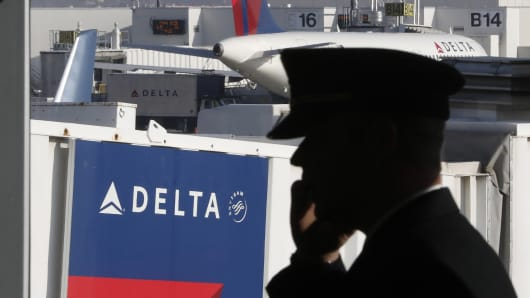 A pilot talks on a mobile device near a Delta Air Lines gate at the Salt Lake City International Airport.