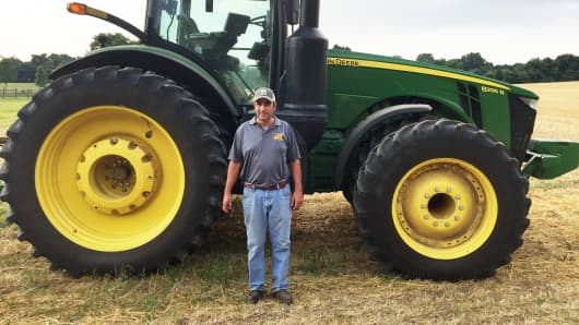 Farmer Bill Beam standing with a tractor on one of his fields near Elverson, PA.