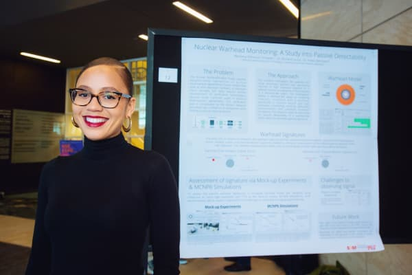 Mareena Robinson Snowden stands in front of a poster about nuclear engineering at MIT.