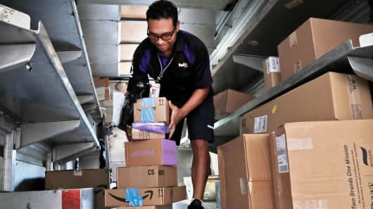 In this Tuesday, July 17, 2018 photo, a FedEx employee delivers packages in Miami.