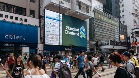 Pedestrians in Hong Kong walk past signage for banks.