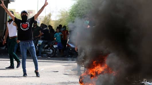 An Iraqi protester gestures near a burning tyre during a demonstration in Basra on July 15, 2018.