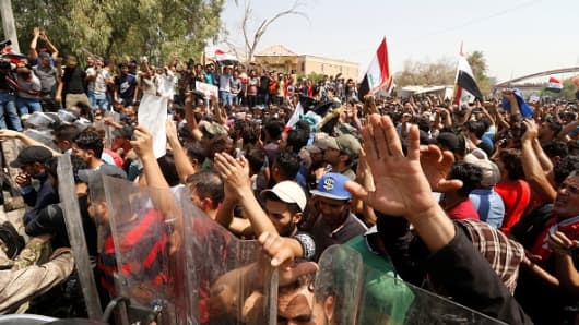 Iraqi citizens shout slogans as they gather to protest against government due to lack of basic services and frequent power outages in front of the governor's building in Iraqs oil-rich Basra province on July 15, 2018.