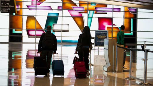 Travelers walk through San Diego International Airport in San Diego.