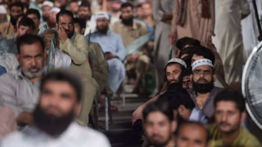 Supporters of head of Pakistani militant organisation Jamaat-ud-Dawa (JuD) Hafiz Saaed look on and listen as they meet the members of the newly formed political party Allah-o-Akbar Tehreek, during a campaign meeting in Islamabad, on July 21, 2018, ahead of the general election. - Pakistan will hold the general election on July 25, 2018.