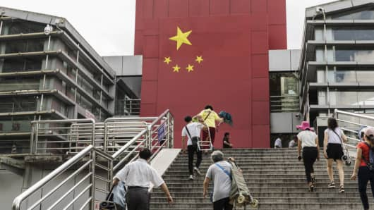 People walk up a flight of stairs as a Chinese flag is displayed at a border crossing facility in the Sha Tou Jiao Port of Shenzhen, China, on Friday, May 18, 2018.