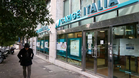 A pedestrian passes a Banca Carige SpA bank branch in Rome, Italy.