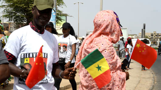 People wave Chinese and Senegalese flags upon the arrival of Chinese President Xi Jinping on July 21, 2018, in Dakar, Senegal.