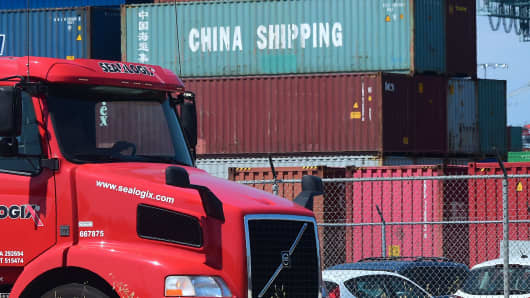 A container delivery truck drives past stacked piles of shipping containers at the Port of Long Beach in Long Beach, California on July 6, 2018, including one from China Shipping, a conglomerate under the direct administration of China's State Council.