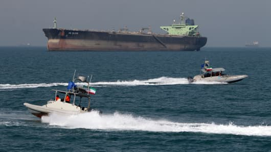 Iranian Revolutionary Guards drive speedboats in front of an oil tanker at the port of Bandar Abbas