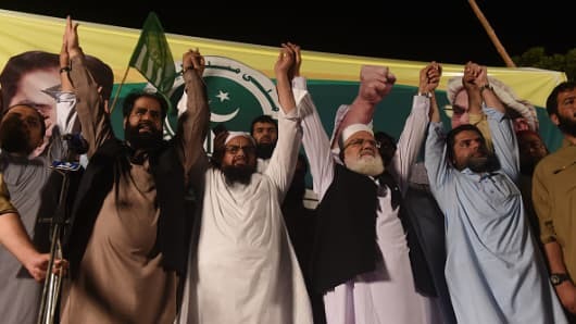Head of Pakistani banned organisation Jamaat-ud-Dawa (JuD) Hafiz Saaed (3L) raises hands with members of his newly formed political party Allah-o-Akbar Tehreek at the election campaign meeting in Lahore ahead of the general election.