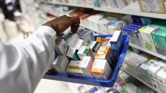 A pharmacist collects medications for prescriptions at a pharmacy.