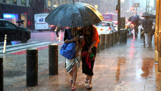 People take cover from the rain in Midtown New York on as a sudden storm hit the area with flash food warning in the tri-state area.