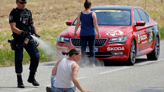 A police officer pepper sprays a protester as another protester stands in front of the race director's car. REUTERS/Stephane Mahe