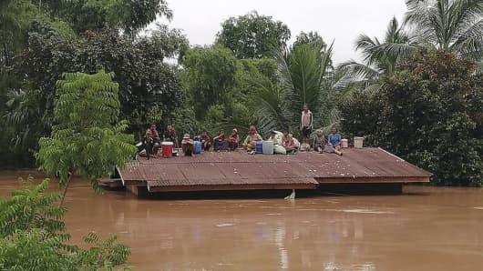 Villagers take refuge on a rooftop above flood waters from a collapsed dam in the Attapeu district of southeastern Laos.