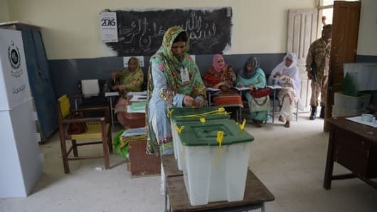 An election official seals ballot boxes before people vote during Pakistan's general election at a polling station in Islamabad on July 25, 2018.