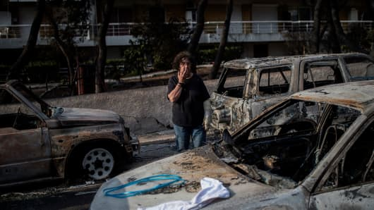 A woman with a cast stands among cars burnt following a wildfire at the village of Mati, near Athens, on July 24, 2018