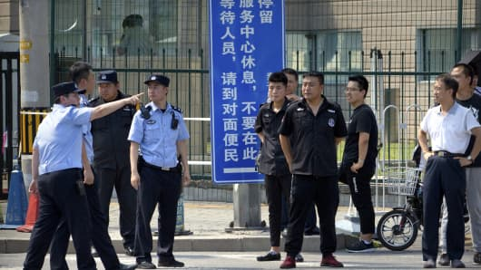 Chinese security personnel stand outside the U.S. Embassy, in the background, after a reported blast occurred nearby in Beijing, Thursday, July 26, 2018.