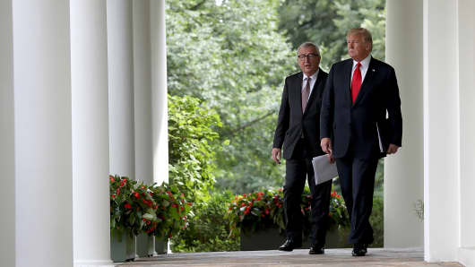 U.S. President Donald Trump and European Commission President Jean-Claude Juncker walk to the Rose Garden of the White House to deliver a joint statement on trade July 25, 2018 in Washington.