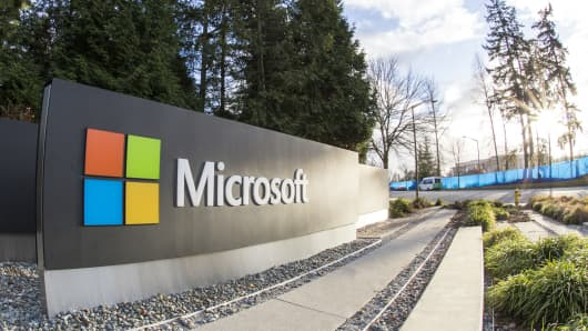 One of the biggest Microsoft signs is placed next to green trees at a public intersection near Microsoft's Redmond campus