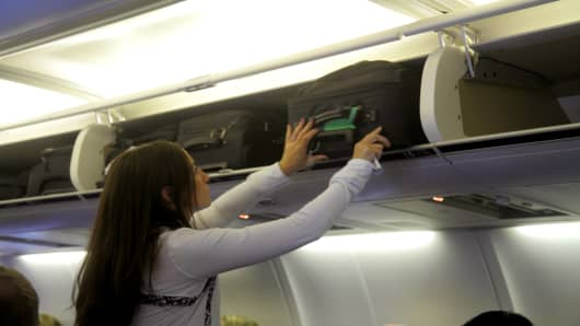 A woman putting her suitcase in an overhead luggage bin on an American  Airlines plane at 142e31ba635c5