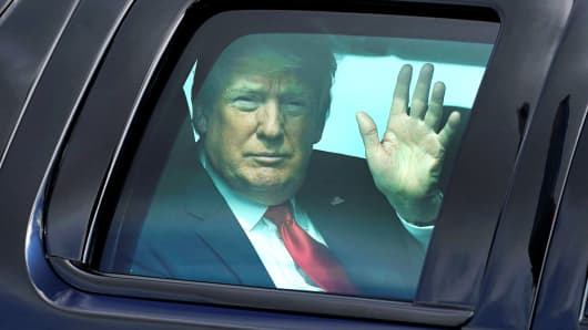 President Donald Trump waves from his vehicle as he prepares to depart for Dubuque, Iowa, from Joint Base Andrews in Maryland, July 26, 2018.