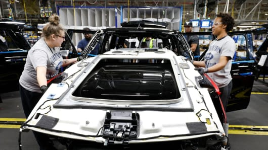 Workers build a truck as it goes through the assembly line at the Ford Kentucky Truck Plant in Louisville, Kentucky.