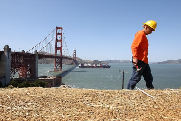 A construction worker makes last minute repairs to a pedestrian walkway and bike path near the Golden Gate Bridge.