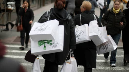 Shoppers carrying bags walk up Fifth Avenue in New York City.